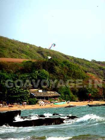 a paraglider in the air over anjuna beach